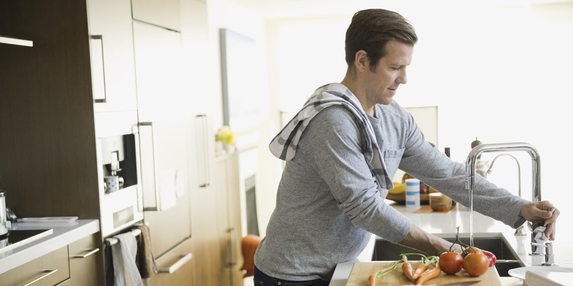 Man washing vegetables in kitchen